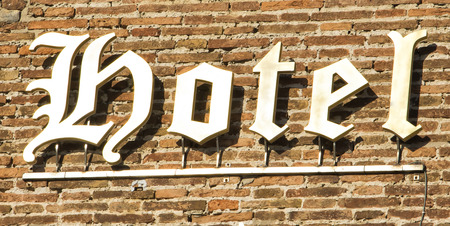 The heraldic characters hotel sign on the brick wall. Florence, Italy.