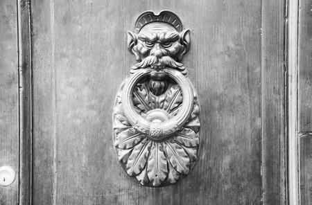 rustiness: Door Knocker on a door, Siena, Tuscany, Italy (black and White). Stock Photo