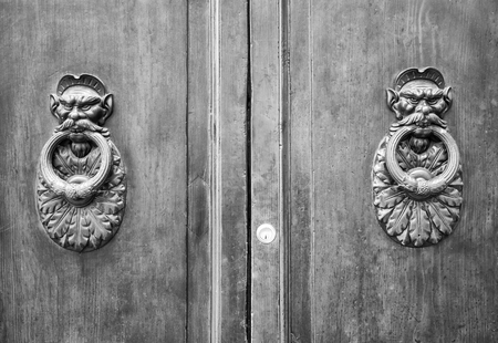 rustiness: Door Knockers on a door, Siena, Tuscany, Italy (Black and White). Stock Photo