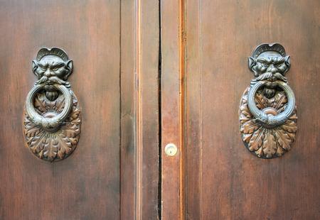 rustiness: Door Knockers on a door, Siena, Tuscany, Italy. Stock Photo