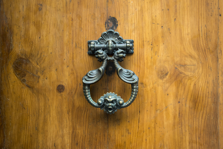 rustiness: Doorknocker on allwood door, Siena, Tuscany. Stock Photo