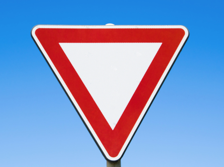 Red and white traffic sign on blue sky.