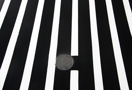 Pedestrian crossing road marking, white lines over black asphalt pavement with almonds.
