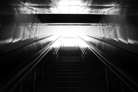 Stairs leading out of concrete pedestrian subway to the city. Concept of success (black and white).