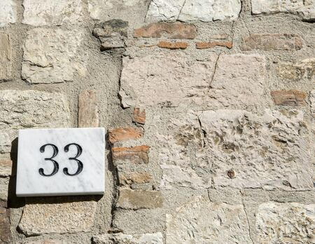 numero: House number 33 sign.