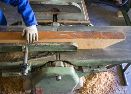 Carpenter workplace. Man using saw to cut wood. 版權商用圖片