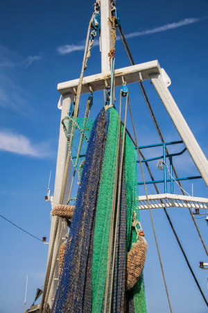 commercial fishing net: A commercial fishing boat with a net staged for a fishing trip