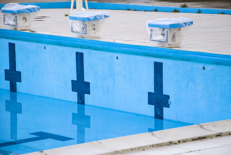 Empty swimming pool with swimming starting blocks.