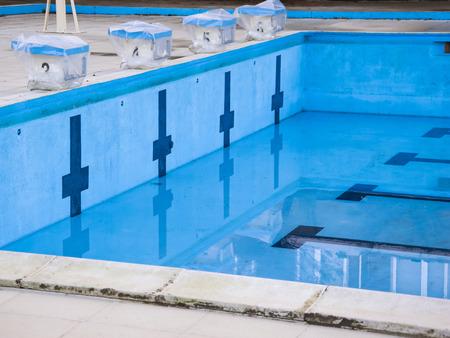 Empty swimming pool with swimming starting blocks.