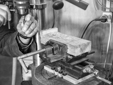 chuck: Carpenter workplace- Man change the Chuck on a drill press. Stock Photo
