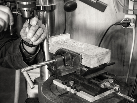 Carpenter workplace- Man change the Chuck on a drill press, antique effect (sepia).