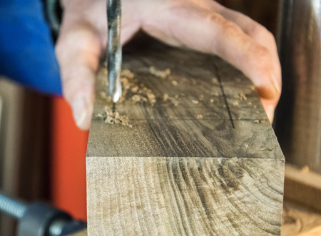 Joinery- drill press on wood close up.