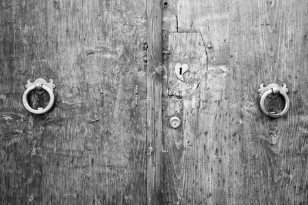 Lion head knockers on an old wooden door in Tuscany, Italy, black and white.