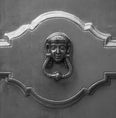 Lion head knockers on an old wooden door in Tuscany ? ? Italy, black and white.