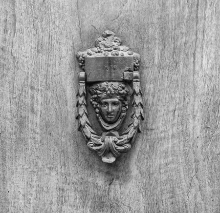 Lion head knockers on an old wooden door in Tuscany