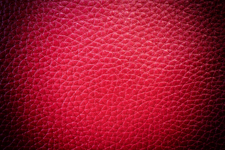 Red leather background with rough surface, vignetting effect.