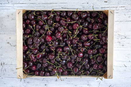 Box of fresh ripe cherries on rustic wooden background Stock Photo