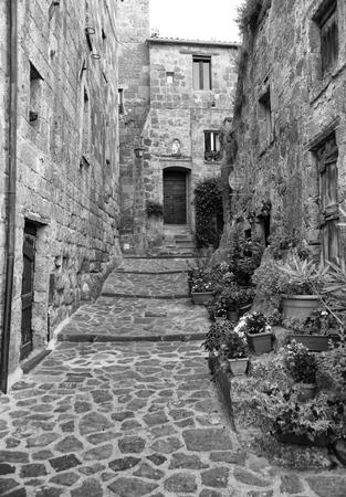 Beautiful view of idyllic alley way in famous Civita di Bagnoregio near Tiber river valley, Lazio, Italy. Black and white