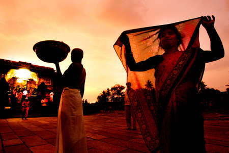 karnataka culture: Belur, India - October 8, 2011: Indian woman covering face with his sari at the side of the snack street vendor, near sunset. The Keshua Temple can be seen in the background, Belur, estate Karnataka, India