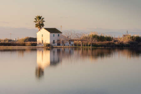 Beautiful landscape with farmhouse in Albufera lagoon, reflection, blue sky and yellow sunlight in sunrise in Natural Park of Albufera, Valencia, Spain