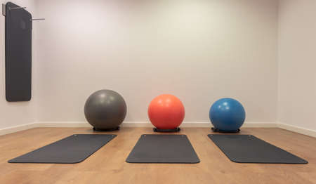 Gym for fitness exercises. Fitball and mat lie on the wooden floor. Fitness, sport, training, gym and lifestyle concept background