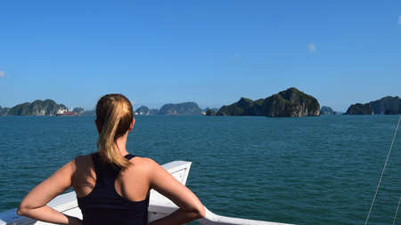blonde woman on her back contemplates the scenery on a cruise ship sailing through halong bay, vietnam, south asia