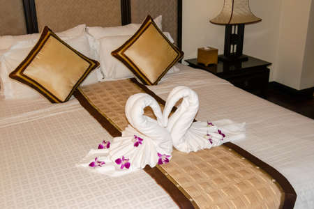 Beautiful hotel for honeymoon sweet.Swan couple put on honeymoon bed. two swans made from towels are kissing on honeymoon white bed. 写真素材