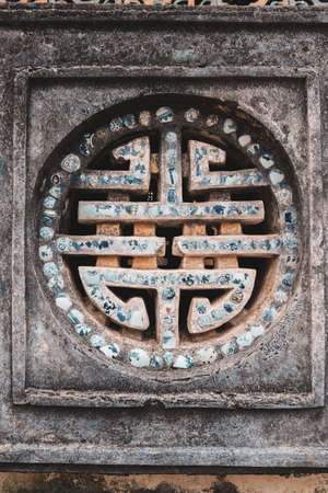 vietnamese stone wall art, symbol on a lilac wall in the Royal Palace in the ancient imperial city of Hue, Vietnam Reklamní fotografie