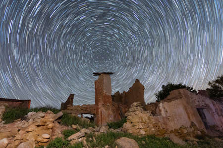 Night landscape of ruins abandoned. . magic stars slow motion rotating above earth. Abstract concept 写真素材