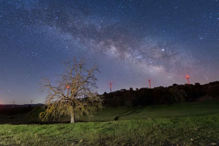 Night sky shot over the harvested field. Milky way galaxy. Countryside Rural Landscape