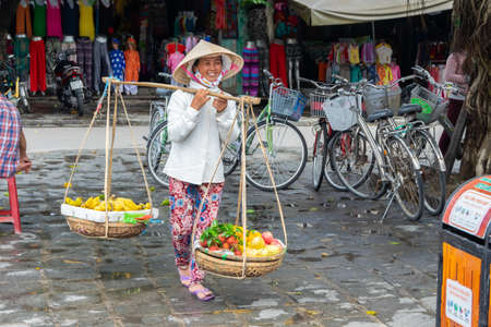 Smiling woman street vendors selling fresh vegetables in the traditional way in Vietnam.