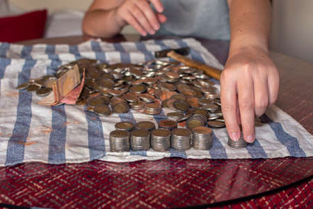 Two hands selecting coins from a piggy bank on a table - Close-up Stockfoto