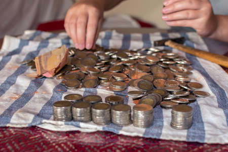 Many coins from a piggy bank and two hands selecting them on a table - Close-up Stockfoto