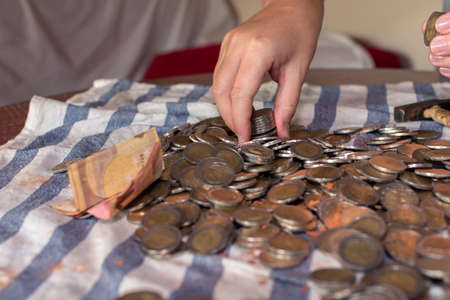 Two womens hands selecting many coins scattered on a table - Top view