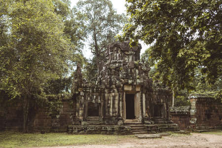 A ruined temple made of rustic rocks in Ankgor Thom, Cambodia surrounded and covered by a lot of vegetation - World Heritage by UNESCO in 1992 - Colorful photo