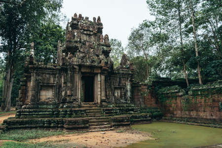 Beautiful and colourful temple in Ankgor Thom, Cambodia surrounded and covered by a lot of green vegetation - UNESCO World Heritage in 1992 - Colourful photo