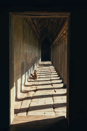 A lugubrious corridor made of rocks in the ruins of the Bayon temple in Ankgor Thom, Cambodia - World Heritage by UNESCO in 1992 - Vertical image