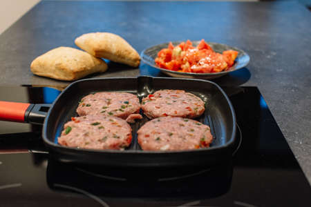 Raw Cutlet meat on the pan Two piece of bread and tomato salad background.