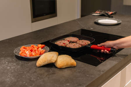 Four piece of Raw Cutlet meat on the pan being cooked in the electric kitchen. And some appetizer aside.