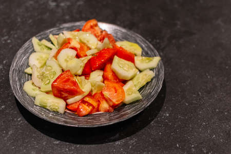 Cucumber and tomato chopped on a little plate. Salad, Fresh salad.