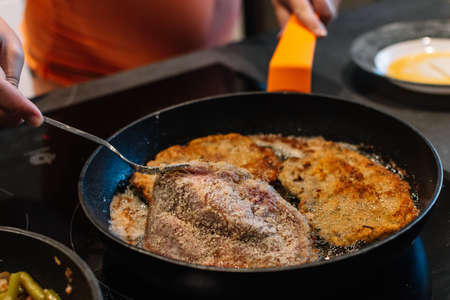 turning over a piece of breaded pork in the pan for dinner. Spanish food