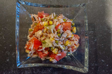 top view of a rice salad, rice, tomato, green beans, cucumber and pepper.
