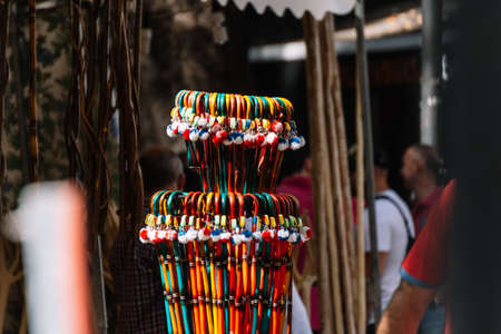 Selective focus on little wooden canes as a souvenir for decorations. Blurry people background