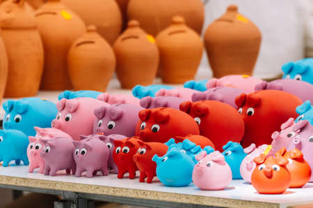 Close up of colorful Piggy Banks And Other Potteries. Selection of terracotta pots, vase and large money pots for sale.