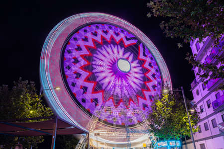 Rotating In Natural Motion Effect Illuminated Attraction Ferris Wheel On Summer Evening Stock fotó