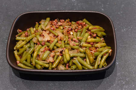 Personal portion of green beans with serrano ham. Spanish cuisine. Stock fotó