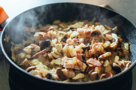 close up of delicious mushrooms with onions and bacon in the pan. Food and texture concept.