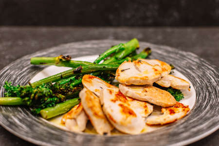 plate of grilled turkey fillet with bimi broccoli. Close up. Black background