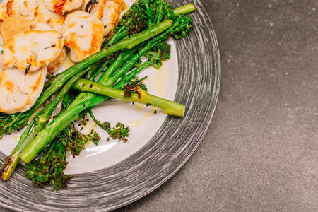 Cooked broccolini with turkey fillet on a plate. Copy space
