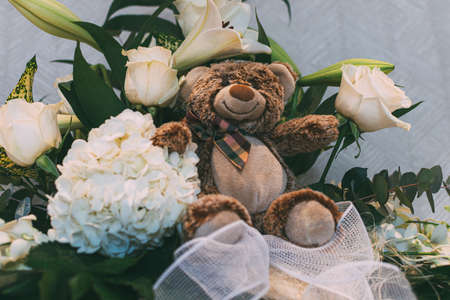 Brown teddy bear between a white flowers bouquet and green leaf. White background Stock fotó